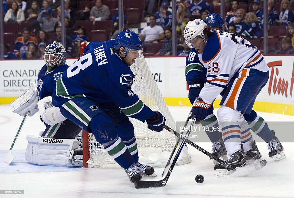 Ryan Jones #28 of the Edmonton Oilers tries to get through Chris Tanev and Cam Barker #18 of the Vancouver Canucks while goalie <a gi-track='captionPersonalityLinkClicked' href=/galleries/search?phrase=Cory+Schneider&family=editorial&specificpeople=696908 ng-click='$event.stopPropagation()'>Cory Schneider</a> #35 of the Vancouver Canucks looks on during third period of NHL action on April 04, 2013 at Rogers Arena in Vancouver, British Columbia, Canada.
