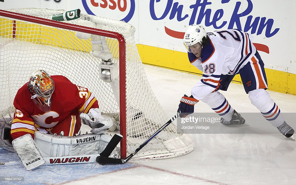 Ryan Jones #28 of the Edmonton Oilers tries to tip the puck past goalie <a gi-track='captionPersonalityLinkClicked' href=/galleries/search?phrase=Joey+MacDonald&family=editorial&specificpeople=2234367 ng-click='$event.stopPropagation()'>Joey MacDonald</a> #35 of the Calgary Flames at Scotiabank Saddledome on April 3, 2013 in Calgary, Alberta, Canada.