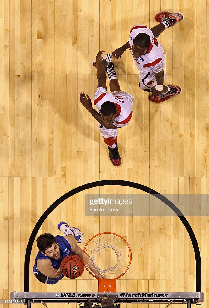 Ryan Kelly #34 of the Duke Blue Devils drives for a shot attempt past Russ Smith #2 and Gorgui Dieng #10 of the Louisville Cardinals during the Midwest Regional Final round of the 2013 NCAA Men's Basketball Tournament at Lucas Oil Stadium on March 31, 2013 in Indianapolis, Indiana.
