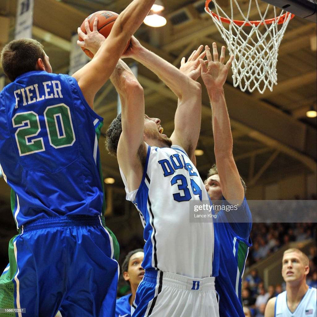 Ryan Kelly #34 of the Duke Blue Devils goes to the hoop against Chase Fieler #20 of the Florida Gulf Coast Eagles at Cameron Indoor Stadium on November 18, 2012 in Durham, North Carolina.