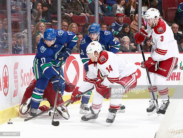 Ryan Kesler and Mike Santorelli of the Vancouver Canucks battle for the puck with Jeff Halpern and Keith Yandle of the Phoenix Coyotes during their...