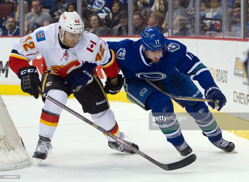 Ryan Kesler #17 of the Vancouver Canucks battles with Mark Cundari #42 of the Calgary Flames for the puck during the second period in NHL action on April 13, 2014 at Rogers Arena in Vancouver, British Columbia, Canada.