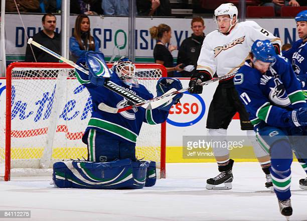 Ryan Kesler of the Vancouver Canucks blocks a shot in front of his goaltender Curtis Sanford with Steve Montador of the Anaheim Ducks at the top of...