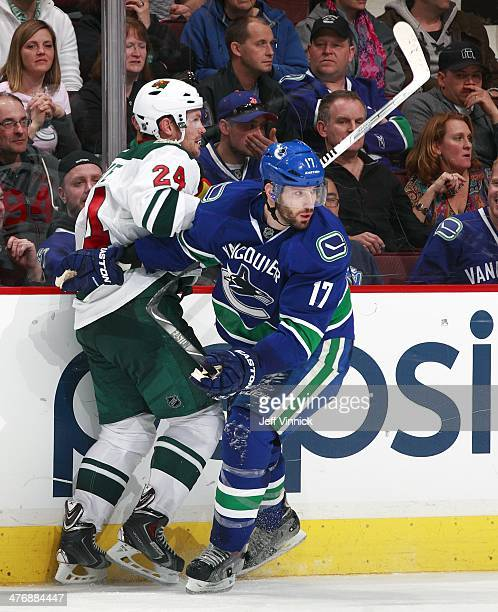 Ryan Kesler of the Vancouver Canucks checks Matt Cooke of the Minnesota Wild during their NHL game at Rogers Arena February 28 2014 in Vancouver...