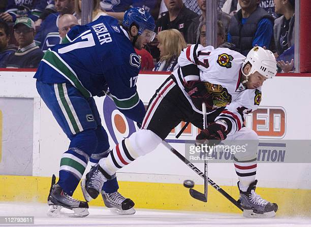 Ryan Kesler of the Vancouver Canucks checks Ryan Johnson of the Chicago Blackhawks as he clear the puck during the first period in Game Five of the...