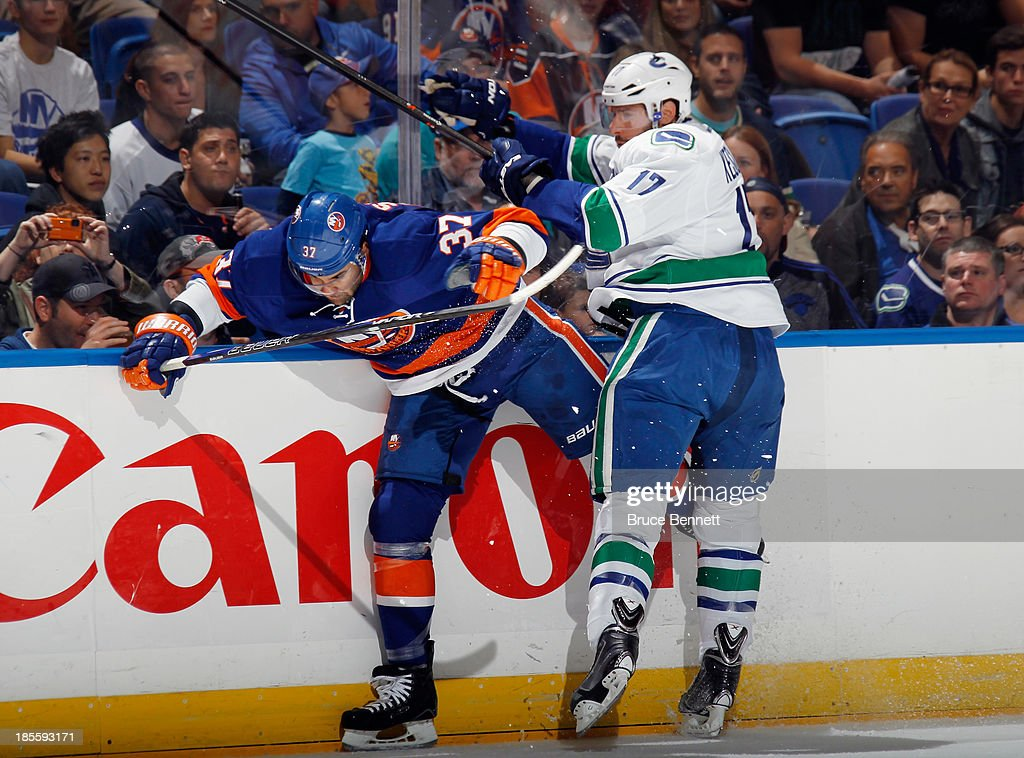 <a gi-track='captionPersonalityLinkClicked' href=/galleries/search?phrase=Ryan+Kesler&family=editorial&specificpeople=206915 ng-click='$event.stopPropagation()'>Ryan Kesler</a> #17 of the Vancouver Canucks collides with <a gi-track='captionPersonalityLinkClicked' href=/galleries/search?phrase=Brian+Strait&family=editorial&specificpeople=570466 ng-click='$event.stopPropagation()'>Brian Strait</a> #37 of the New York Islanders during the first period at the Nassau Veterans Memorial Coliseum on October 22, 2013 in Uniondale, New York.