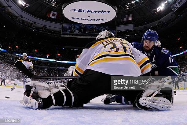 Ryan Kesler of the Vancouver Canucks falls after losing his balance while trying to shoot against Tim Thomas of the Boston Bruins during game one of...