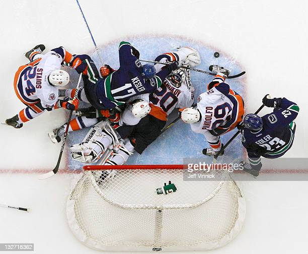Ryan Kesler of the Vancouver Canucks falls on top of Evgeni Nabokov of the New York Islanders at Rogers Arena November 13 2011 in Vancouver British...