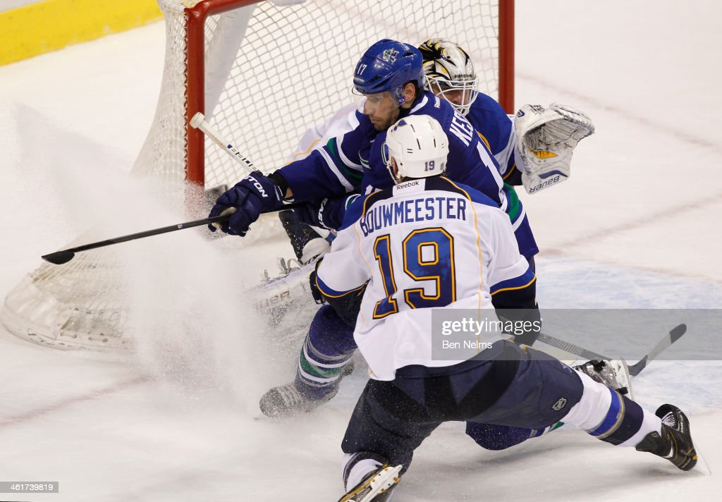 Ryan Kesler of the Vancouver Canucks is checked into goaltender Brian Elliott of the St Louis Blues by Jay Bouwmeester during the third period of...