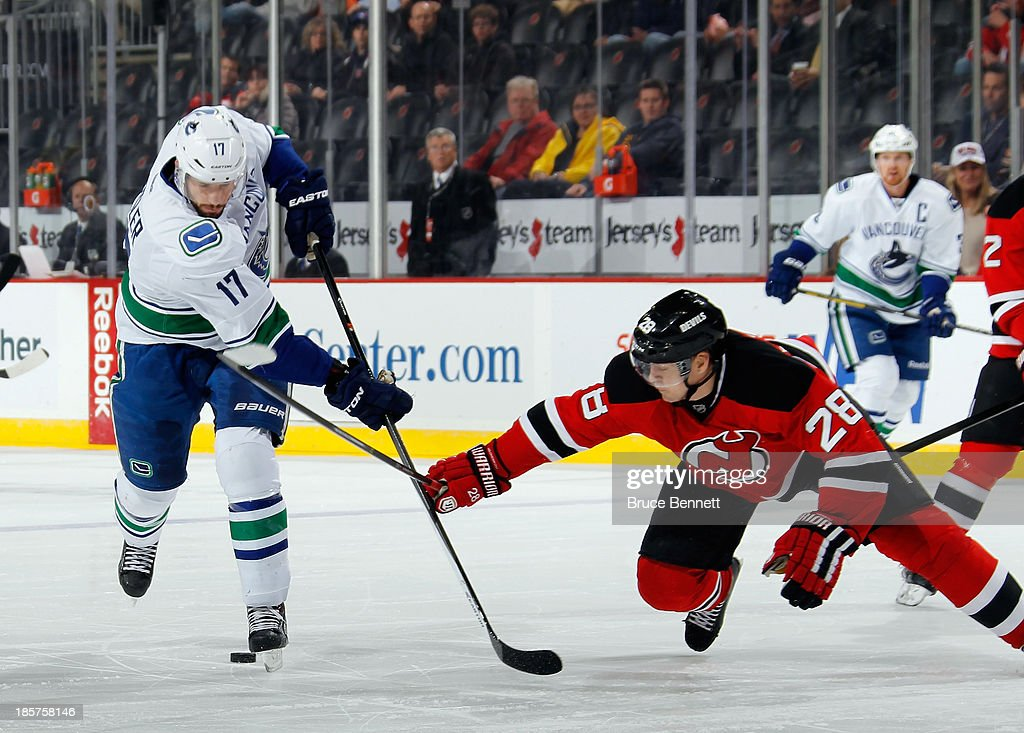 Ryan Kesler #17 of the Vancouver Canucks is poke checked by Anton Volchenkov #28 of the New Jersey Devils during the first period at the Prudential Center on October 24, 2013 in Newark, New Jersey.