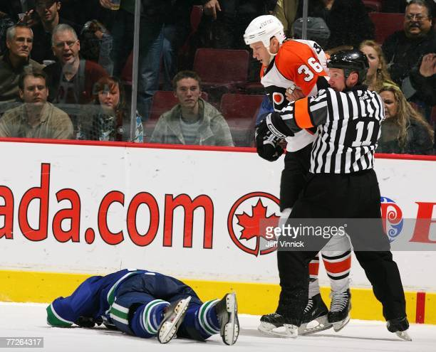 Ryan Kesler of the Vancouver Canucks lays motionless on the ice as Jesse Boulerice of the Philadelphia Flyers is held back by referee Kelly...
