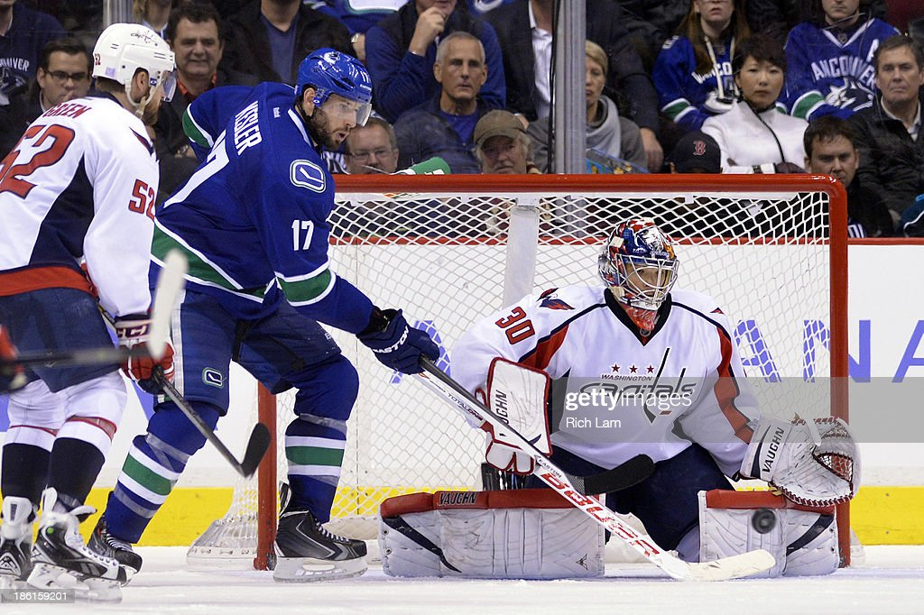 <a gi-track='captionPersonalityLinkClicked' href=/galleries/search?phrase=Ryan+Kesler&family=editorial&specificpeople=206915 ng-click='$event.stopPropagation()'>Ryan Kesler</a> #17 of the Vancouver Canucks tries to deflect the puck past goalie <a gi-track='captionPersonalityLinkClicked' href=/galleries/search?phrase=Michal+Neuvirth&family=editorial&specificpeople=3205600 ng-click='$event.stopPropagation()'>Michal Neuvirth</a> #30 of the Washington Capitals during the third period in NHL action on October 28, 2012 at Rogers Arena in Vancouver, British Columbia, Canada. Mike Green #52 of the Washington Capitals tries to help defend on the play.