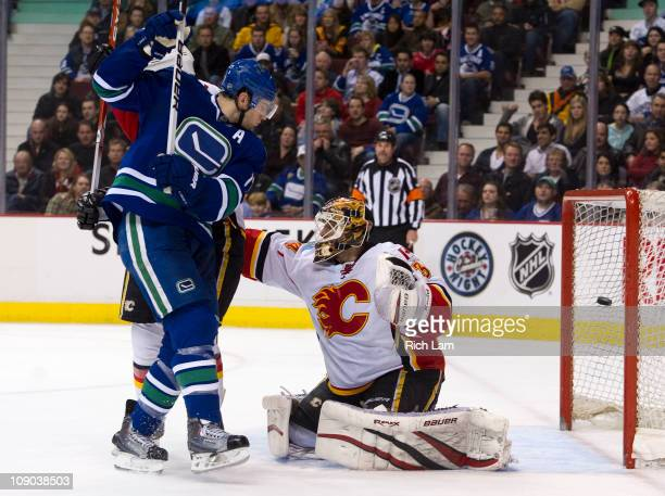 Ryan Kesler of the Vancouver Canucks watches teammate Mikael Samuelsson's shot hit the back of the net past goalie Miikka Kiprusoff of the Calgary...