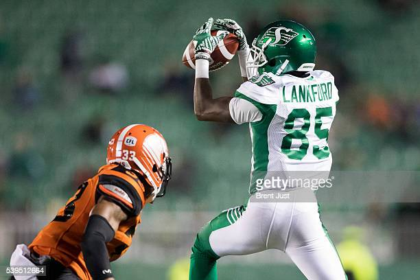 Ryan Lankford of the Saskatchewan Roughriders goes up to make a catch in front of Dino Teague of the BC Lions in the preseason game between the BC...