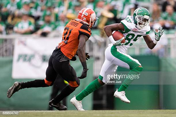 Ryan Lankford of the Saskatchewan Roughriders tries to escape fro Davarus Shores of the BC Lions in the preseason game between the BC Lions and...