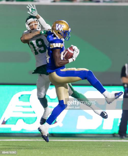 Ryan Lankford of the Winnipeg Blue Bombers makes a touchdown catch in front of Mark Roberts of the Saskatchewan Roughriders in the preseason game...
