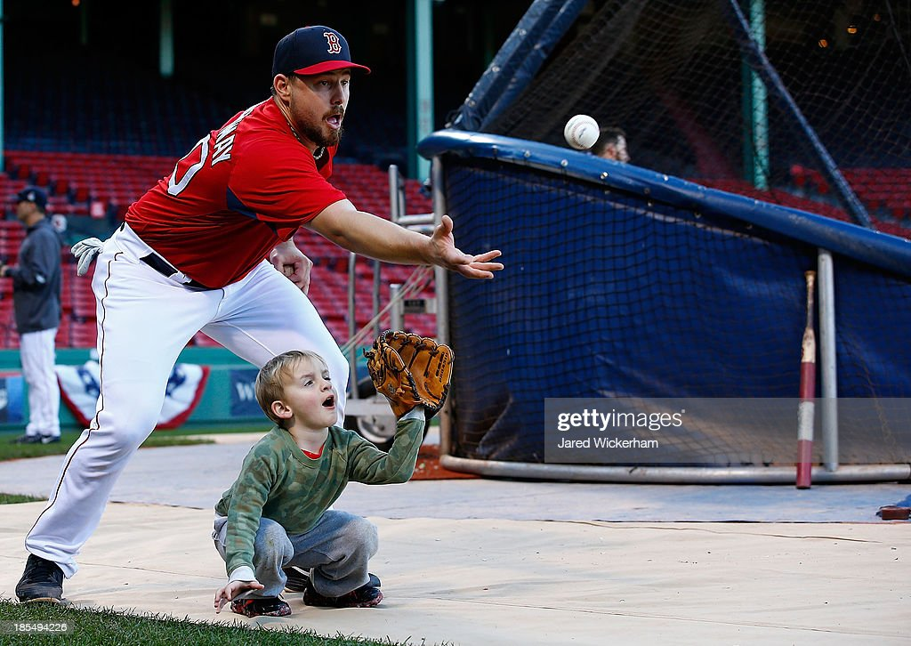 Ryan Lavarnway #20 of the Boston Red Sox catches a ball in front of Hank Drew, the son of Stephen Drew #7 of the Boston Red Sox, during the workout prior to the start of the World Series on October 21, 2013 at Fenway Park in Boston, Massachusetts.