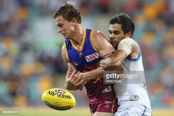 Ryan Lester of the Lions is tackled by Jack Martin of the Suns during the round 21 AFL match between the Brisbane Lions and the Gold Coast Suns at...