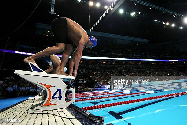 ryan lochte prepares to dive off of the starting block as he competes in the championship