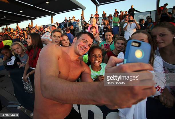 Ryan Lochte takes a photo with a fan after day four of the Arena Pro Swim Series at the Skyline Aquatic Center on April 18 2015 in Mesa Arizona