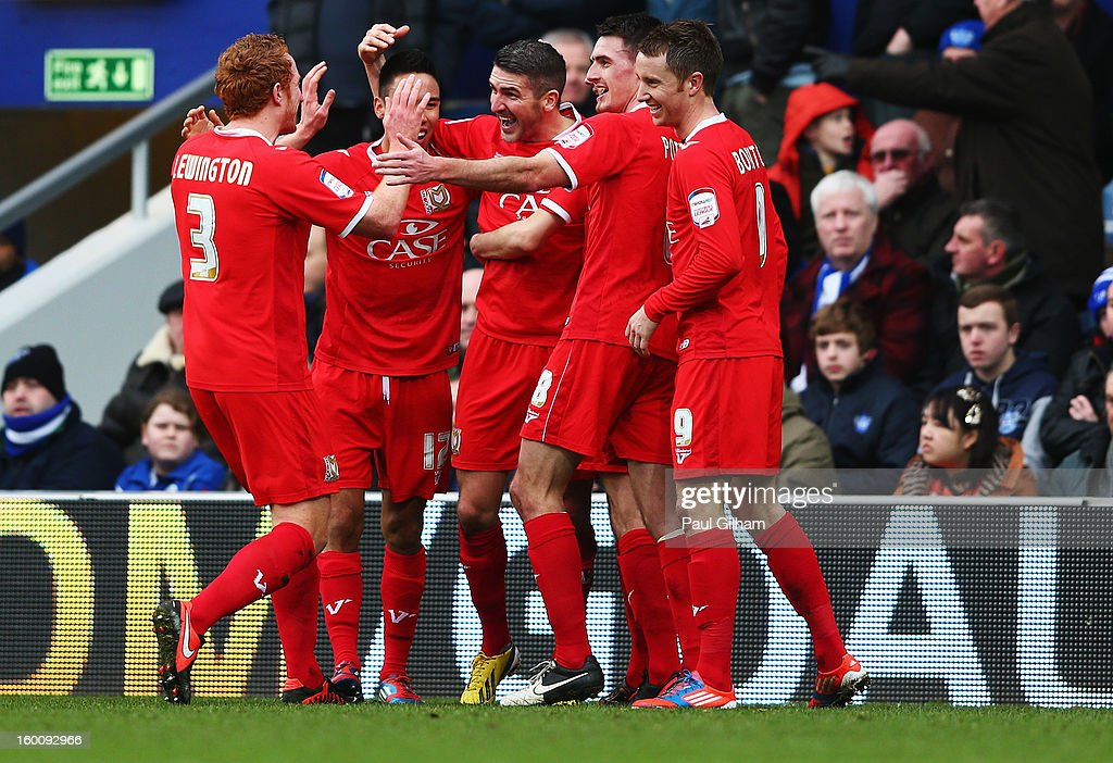 Ryan Lowe (C) of Milton Keynes Dons celebrates with team mates after scoring his sides second goal during the FA Cup with Budweiser Fourth Round match between Queens Park Rangers and Milton Keynes Dons at Loftus Road on January 26, 2013 in London, England.