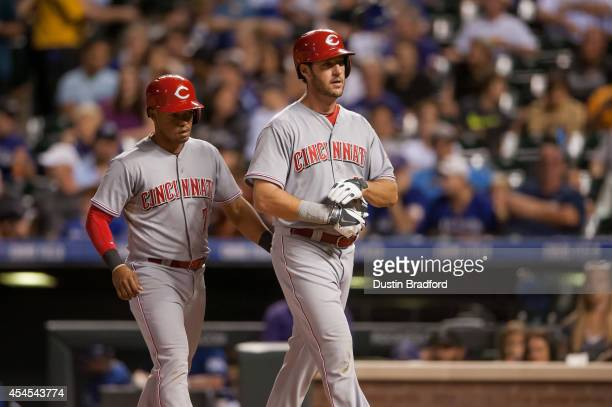 Ryan Ludwick of the Cincinnati Reds walks off the field with Ramon Santiago after hitting a home run in the sixth inning against the Colorado Rockies...