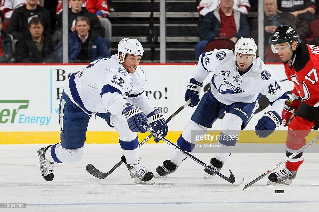 Ryan Malone #12 and Nate Thompson #44 of the Tampa Bay Lightning in action against the New Jersey Devils at the Prudential Center on February 7, 2013 in Newark, New Jersey. The Devils defeated the Lightning 4-2.