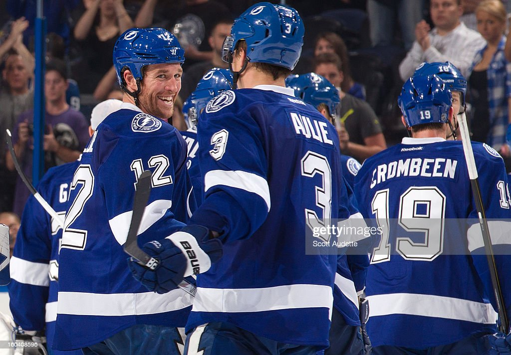 Ryan Malone #12 celebrates with Keith Aulie #3 of the Tampa Bay Lightning against the Florida Panthers at the Tampa Bay Times Forum on January 29, 2013 in Tampa, Florida.