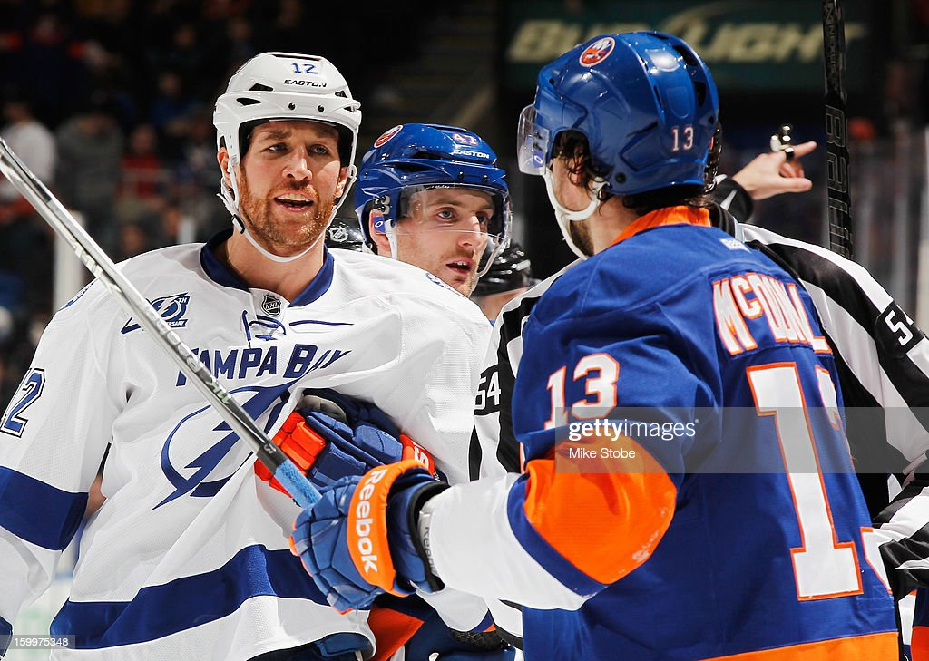 Ryan Malone #12 of the Tampa Bay Lightning and Colin McDonald #13 of the New York Islanders exchange words at Nassau Veterans Memorial Coliseum on January 21, 2013 in Uniondale, New York.