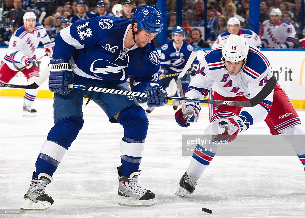 Ryan Malone #12 of the Tampa Bay Lightning battles for the puck with Taylor Pyatt #14 of the New York Rangers during the first period of their game at the Tampa Bay Times Forum on February 2, 2013 in Tampa, Florida.