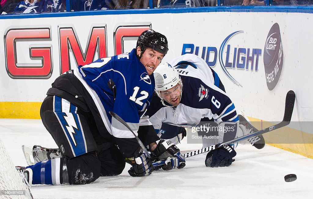 Ryan Malone #12 of the Tampa Bay Lightning battles for the puck with Ron Hainsey #6 of the Winnipeg Jets during the first period of the game at the Tampa Bay Times Forum on February 1, 2013 in Tampa, Florida.
