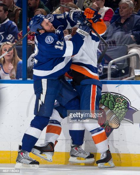 Ryan Malone of the Tampa Bay Lightning checks Matt Martin of the New York Islanders during the second period at the Tampa Bay Times Forum on January...