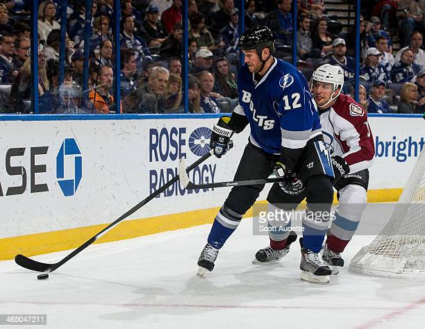 Ryan Malone of the Tampa Bay Lightning controls the puck against Nate Guenin of the Colorado Avalanche during the first period at the Tampa Bay Times...