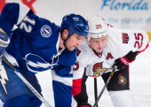 Ryan Malone of the Tampa Bay Lightning faces off against Chris Neil of the Ottawa Senators during the first period at the Tampa Bay Times Forum on...