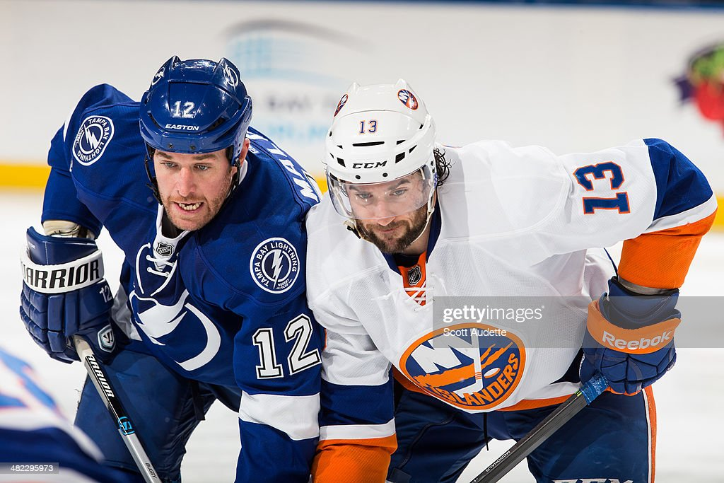 Ryan Malone of the Tampa Bay Lightning faces off against Colin McDonald of the New York Islanders during the first period at the Tampa Bay Times...