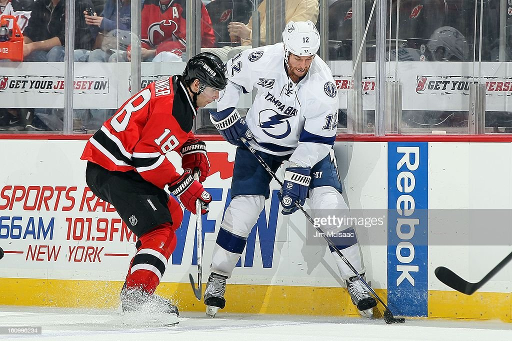 Ryan Malone #12 of the Tampa Bay Lightning in action against Steve Bernier #18 of the New Jersey Devils at the Prudential Center on February 7, 2013 in Newark, New Jersey. The Devils defeated the Lightning 4-2.