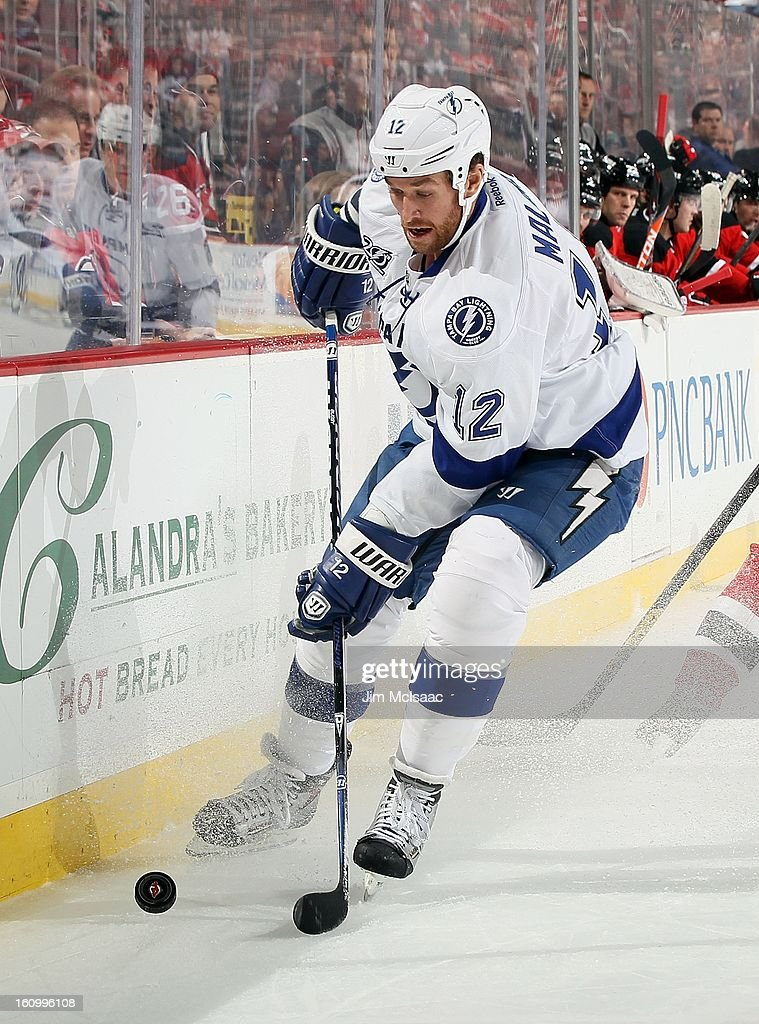 Ryan Malone #12 of the Tampa Bay Lightning in action against the New Jersey Devils at the Prudential Center on February 7, 2013 in Newark, New Jersey. The Devils defeated the Lightning 4-2.