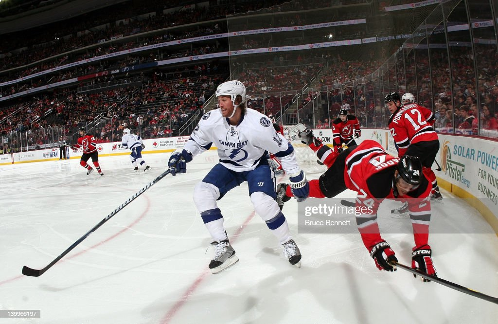 Ryan Malone of the Tampa Bay Lightning knocks Bryce Salvador of the New Jersey Devils off the puck at the Prudential Center on February 26 2012 in...