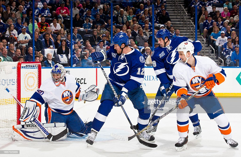 Ryan Malone #12 of the Tampa Bay Lightning looks back at goalie Evgeni Nabokov #20 of the New York Islanders during the first period of the game at the Tampa Bay Times Forum on March 14, 2013 in Tampa, Florida.