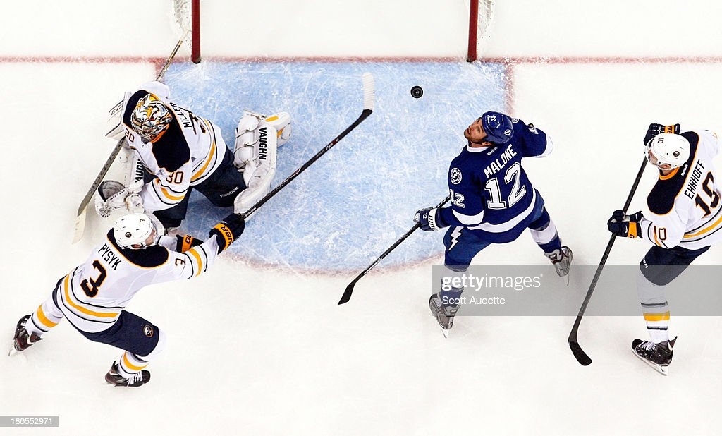 Ryan Malone #12 of the Tampa Bay Lightning looks for the puck in the air while Mark Pysyk #3 of the Buffalo Sabres tries to knock it away from goalie Ryan Miller #30 at the Tampa Bay Times Forum on October 26, 2013 in Tampa, Florida.