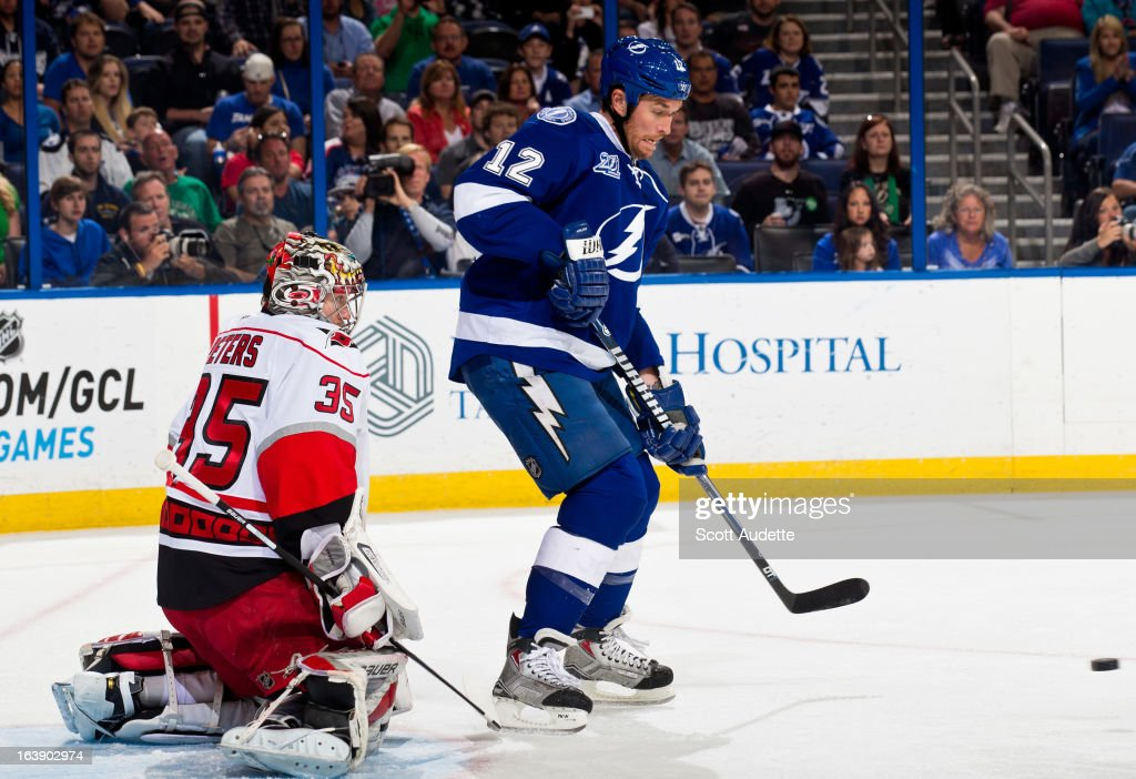 Ryan Malone #12 of the Tampa Bay Lightning passes the puck in front of Justin Peters #35 of the Carolina Hurricanes during the first period of the game at the Tampa Bay Times Forum on March 16, 2013 in Tampa, Florida.