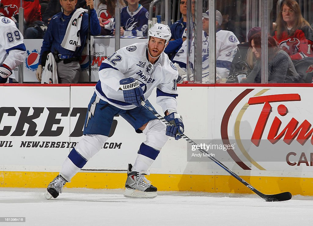 Ryan Malone #12 of the Tampa Bay Lightning plays the puck against the New Jersey Devils during the game at the Prudential Center on February 7, 2013 in Newark, New Jersey.