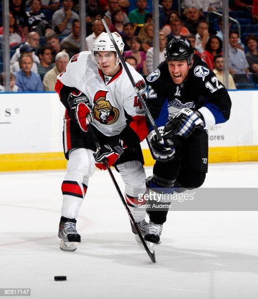 Ryan Malone of the Tampa Bay Lightning shoots the puck against Alexandre Picard of the Ottawa Senators at the St Pete Times Forum on October 29 2009...