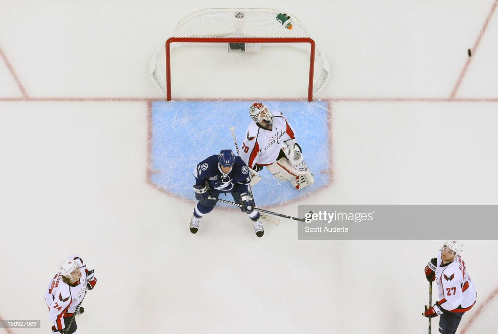<a gi-track='captionPersonalityLinkClicked' href=/galleries/search?phrase=Ryan+Malone&family=editorial&specificpeople=206964 ng-click='$event.stopPropagation()'>Ryan Malone</a> #12 of the Tampa Bay Lightning stands in front of the goal as <a gi-track='captionPersonalityLinkClicked' href=/galleries/search?phrase=Braden+Holtby&family=editorial&specificpeople=5370964 ng-click='$event.stopPropagation()'>Braden Holtby</a> #70, John Carlson #74 and <a gi-track='captionPersonalityLinkClicked' href=/galleries/search?phrase=Karl+Alzner&family=editorial&specificpeople=3938829 ng-click='$event.stopPropagation()'>Karl Alzner</a> #27 of the Washington Capitals look up to spot the puck in the air at the Tampa Bay Times Forum on January 19, 2013 in Tampa, Florida.