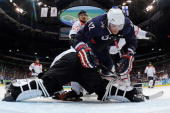 Ryan Malone of the United States falls over goal tender Jonas Hiller of Switzerland in the first period during the ice hockey men's quarter final...