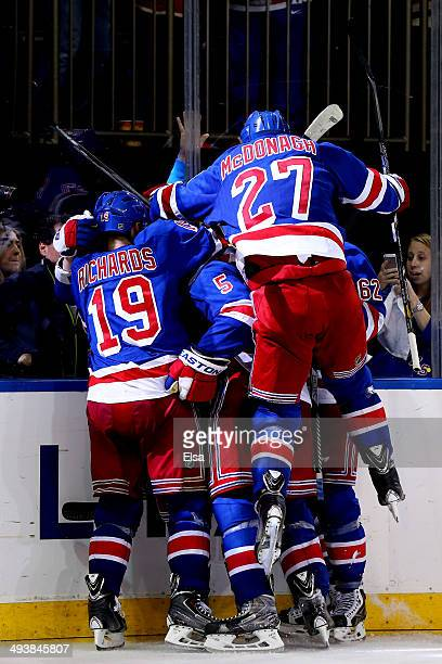 Ryan McDonagh jumps on Martin St Louis of the New York Rangers after St Louis scored the game winning shot in overtime against Dustin Tokarski of the...