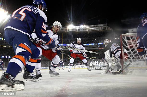Ryan McDonagh of the New York Rangers and Cal Clutterbuck of the New York Islanders vie for the puck to the right of the Islanders net during the...