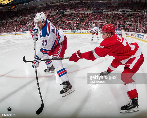 Ryan McDonagh of the New York Rangers battles for the puck along the boards with Dylan Larkin of the Detroit Red Wings during an NHL game at Joe...