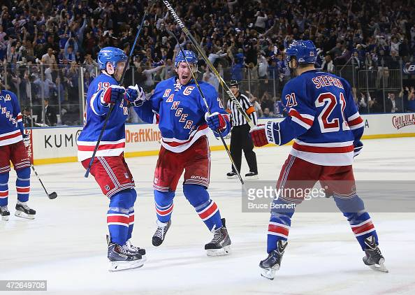 Ryan McDonagh of the New York Rangers celebrates his game winning goal at 937 of overtime against the Washington Capitals and is joined by Jesper...