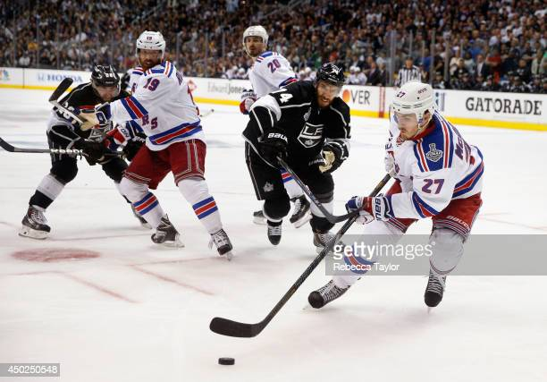 Ryan McDonagh of the New York Rangers controls the puck away from Dwight King of the Los Angeles Kings as Brad Richards and Chris Kreider look on...